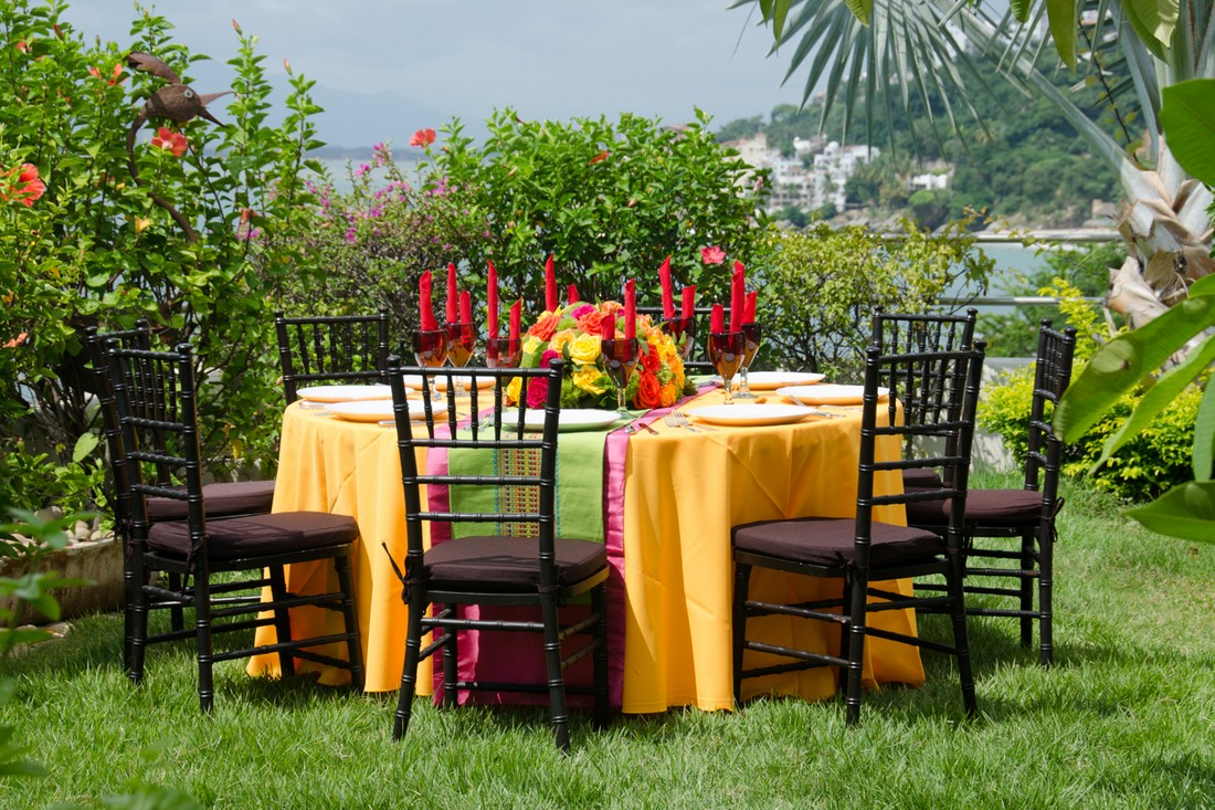 A table setting on a garden, with yellow linen, and black chairs.