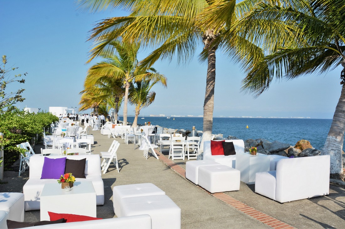 White lounges at the pier with palm trees and blue sky's.