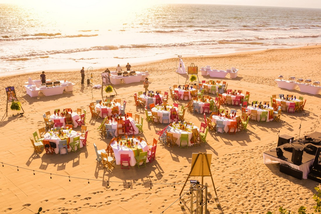 Private event on the beach during a sunset, with colorful Mexican chairs.