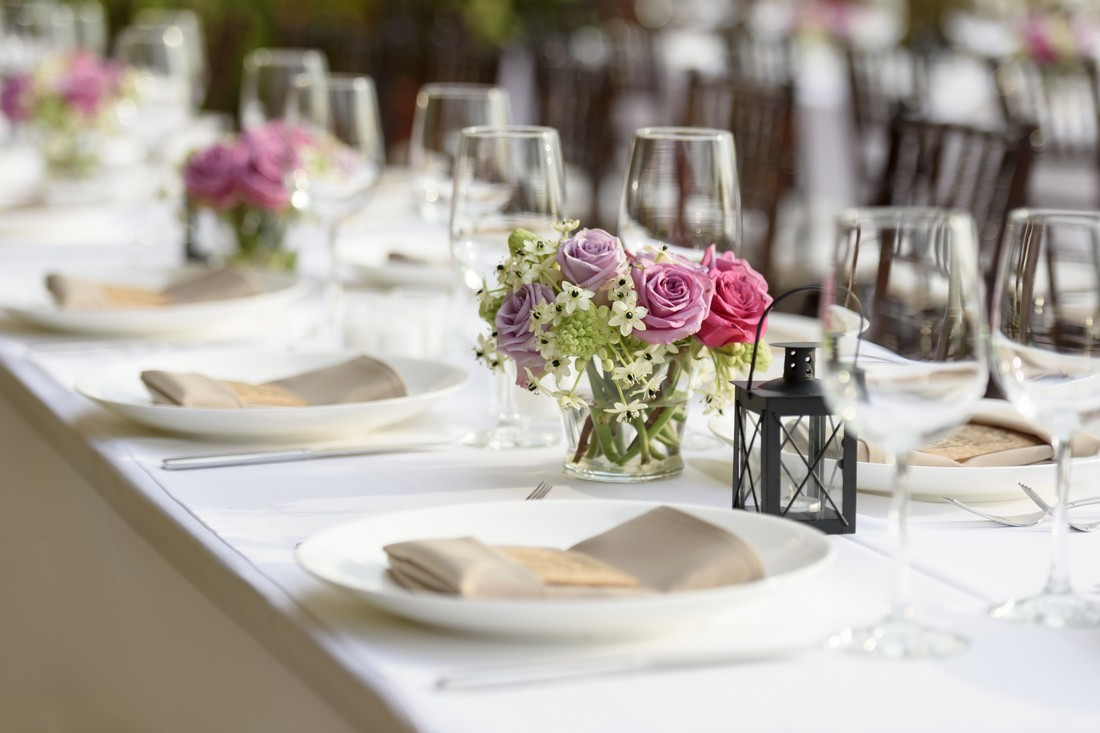 Long table setting with small flower arrangements as centerpieces.